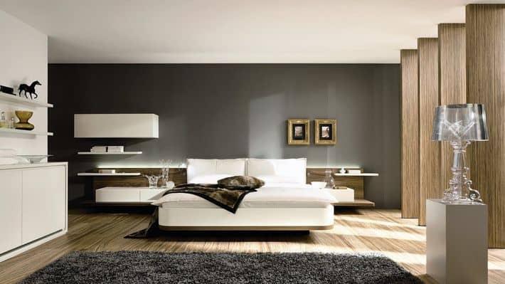 Phòng ngủ của bố mẹ thoáng, sáng nhờ thiết kế hệ cửa sổ kính lớn. Mảng tường xám đầu giường giúp làm nổi bật chiếc giường với ga, gối màu trắng cũng hệ kệ lưu trữ sáng màu.