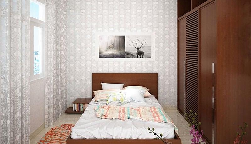 Giường ngủ gỗ với diện tích tương đối, bàn làm việc bố trí sát tường cùng ghế thư giãn gần cửa sổ.