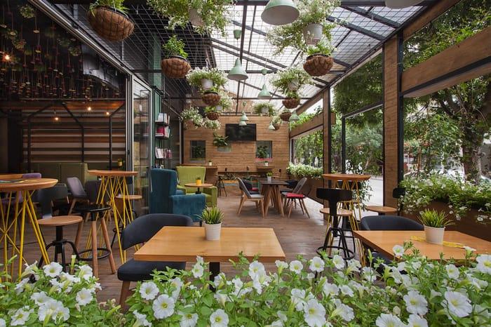 Thiết kế quán mặt tiền rộng với cây xanh trang trí xung quanh